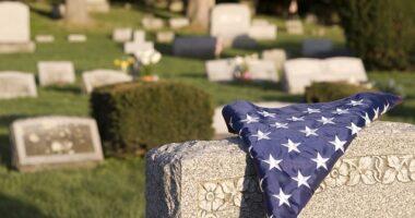 american flag folded on veteran tombstone